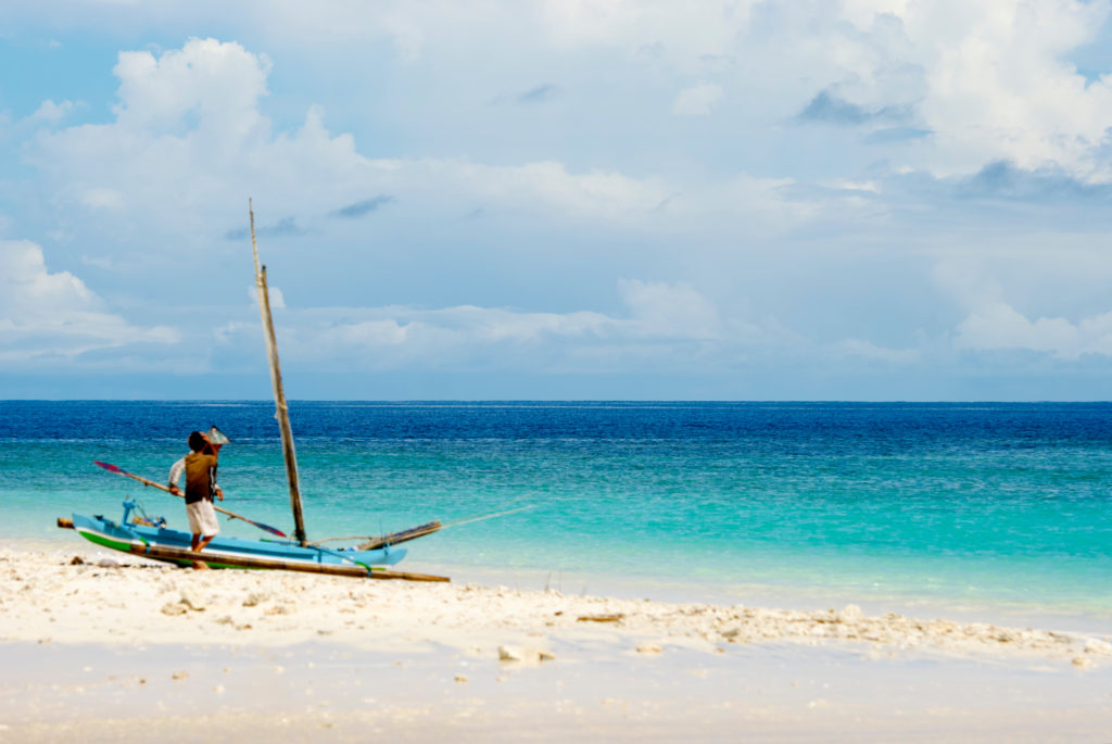 A fisherman prepares a small sailboat as it sits on the sand, set against a a still ocean and cloudy sky.