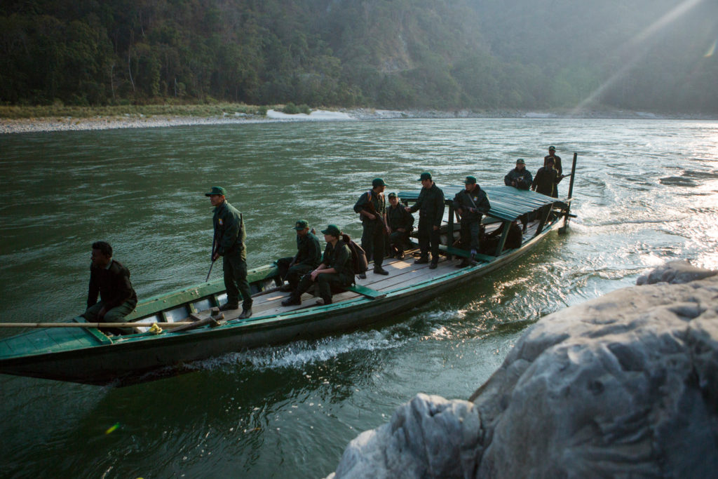 A group of rangers, dressed in dark green clothing and some holding weapons, are standing and sitting on a small, green boat. The boat is traveling along a river- a large rock can be seen on the right in the foreground while the opposite bank of the river and trees stretch in the background.